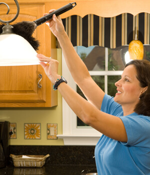 Woman dusting kitchen light