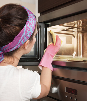 Woman cleaning inside of microwave