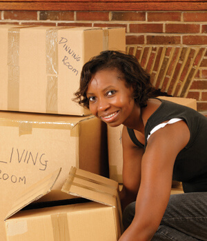 Woman smiling lifting moving box